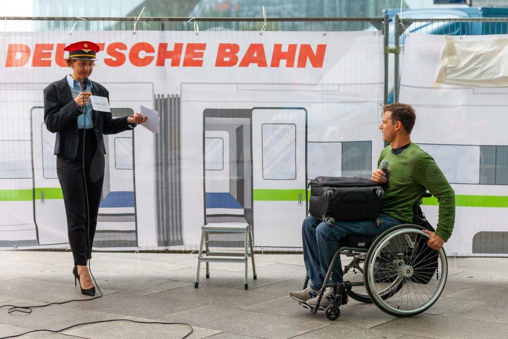 Sketch: Bahnchefin mit Rollinutzendem vor einem Zug mit Stufen