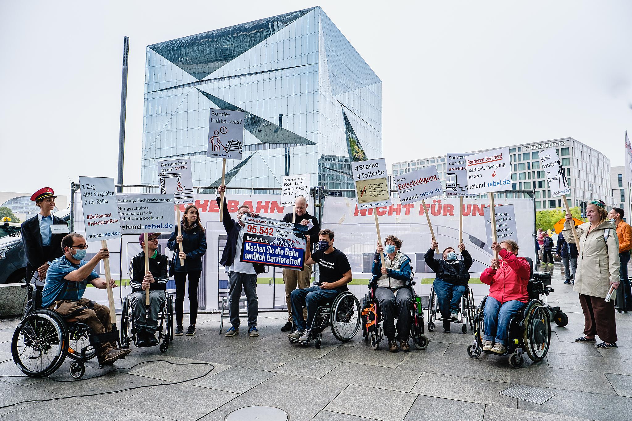 Protestierende mit Rollstuhl und Langstock am Bahnhof Berlin