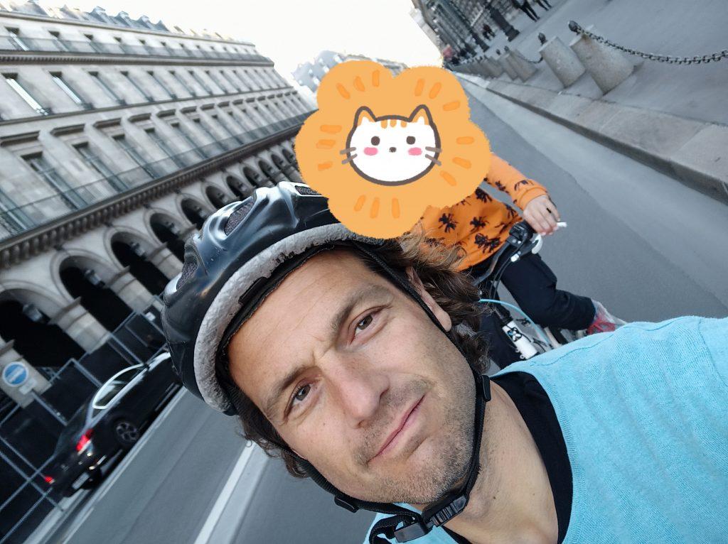 Kopf mit Helm, dahinter unkenntlich gemachtes Kind auf dem Fahrradweg inmitten von Paris